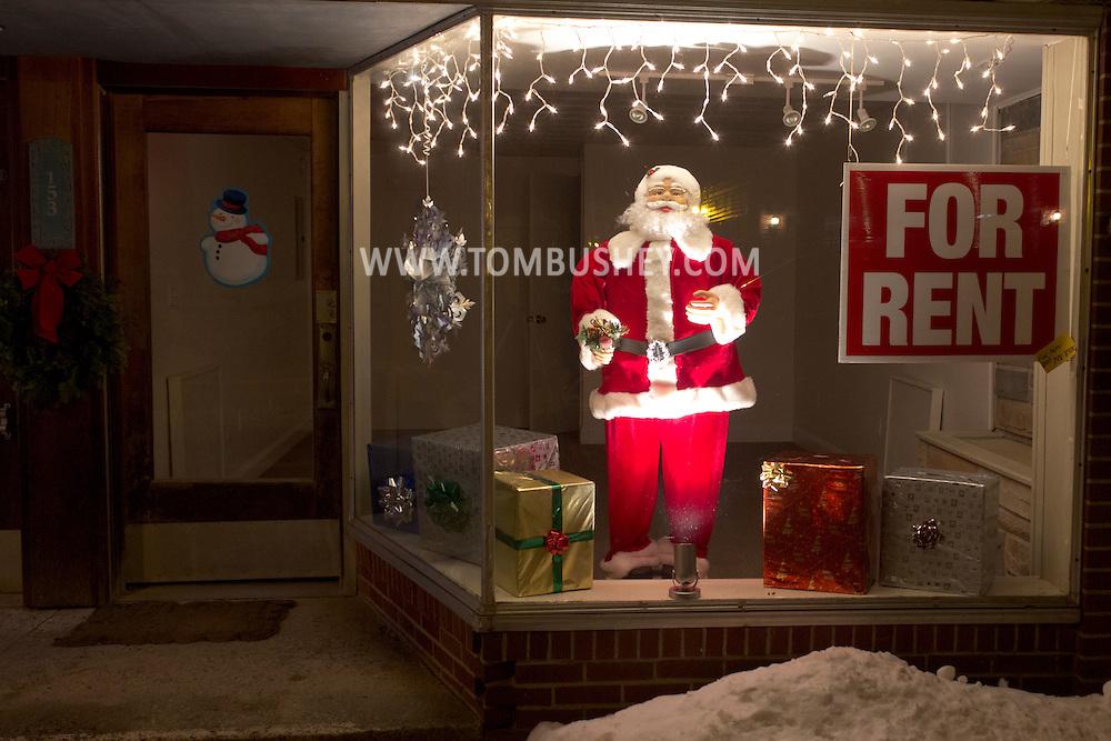 Wurtsboro, New York -  Santa in the window display of a store for rent on Sullivan Street on Jan. 1, 2013. ©Tom Bushey / The Image Works