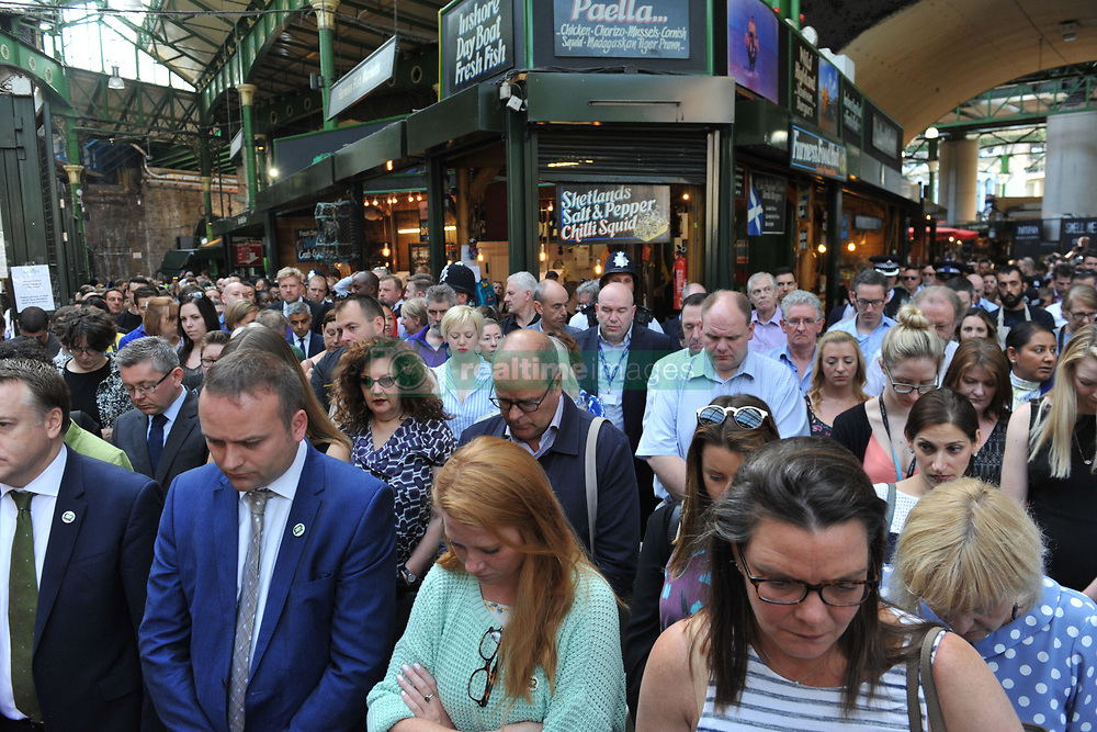 Traders and visitors pause for a minute's silence to remember the victims of the London Bridge terror attack before the market bell is rung to mark the opening of Borough Market.
