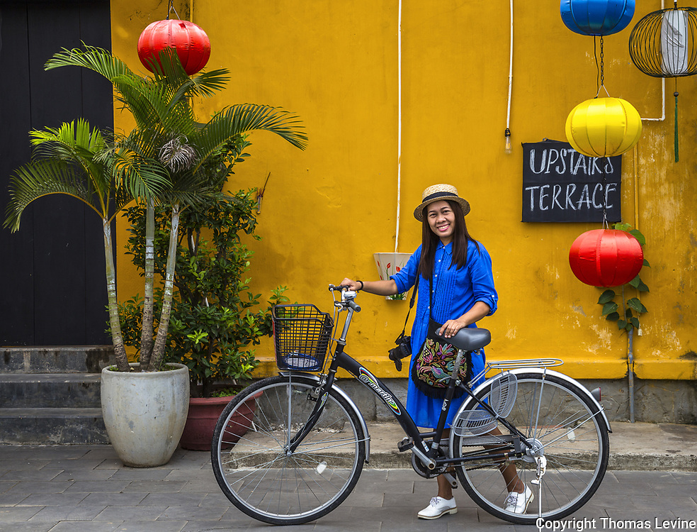 July 29, 2017 Hoi An Ancient Town, Hoian, VN. A lady Tourist in dark blue poses with her bicycle with the Hoi An UNESCO yellow, on the building in the background.