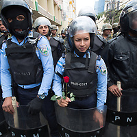 On Women's Day, protestors gave roses to policewomen who were on the streets to stop protestors getting near the National Congress buildings in Tegucigalpa.
