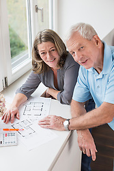 Smiling couple with construction plans