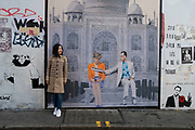 Woman standing next to a paste up street art painting of the famous photograph of Princess Diana at the Taj Mahal on a wall in London, England, United Kingdom. Sitting next to her is a representation of Dodi Fayed.