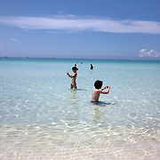 Asian tourists taking photographs in the ocean at White Beach, Boracay Island, the Philippines on October 3, 2008, Photo Tim Clayton..Asian tourists at White Beach, Boracay Island, the Philippines...The 4 km stretch of White beach on Boracay Island, the Philippines has been honoured as the best leisure destination in Asia beating popular destinations such as Bali in Indonesia and Sanya in China in a recent survey conducted by an International Travel Magazine with 2.2 million viewers taking part in the online poll...Last year, close to 600,000 visitors visited Boracay with South Korea providing 128,909 visitors followed by Japan, 35,294, USA, 13,362 and China 12,720...A popular destination for South Korean divers and honeymooners, Boracay is now attracting crowds of tourists from mainland China who are arriving in ever increasing numbers. In Asia, China has already overtaken Japan to become the largest source of outland travelers...Boracay's main attraction is 4 km of pristine powder fine white sand and the crystal clear azure water making it a popular destination for Scuba diving with nearly 20 dive centers along White beach. The stretch of shady palm trees separate the beach from the line of hotels, restaurants, bars and cafes. It's pulsating nightlife with the friendly locals make it increasingly popular with the asian tourists...The Boracay sailing boats provide endless tourist entertainment, particularly during the amazing sunsets when the silhouetted sails provide picture postcard scenes along the shoreline...Boracay Island is situated an hours flight from Manila and it's close proximity to South Korea, China, Taiwan and Japan means it is a growing destination for Asian tourists... By 2010, the island of Boracay expects to have 1,000,000 visitors.