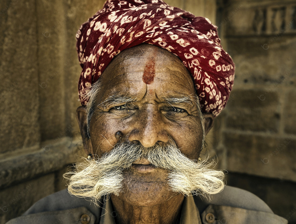 Portrait of man with large moustache and wearing a turban inside the old walled fort of Jaisalmer Rajasthan India. Moustache are an attribute well known for men living in Rajasthan that consider it as a sign of masculinity and social status.