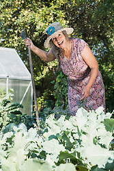 Happy woman with a rake in the garden, Altoetting, Bavaria, Germany