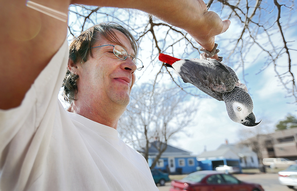 Doug Lindsey enjoys the warmer weather with Pepper, his 6-year-old African grey parrot outside his apartment Friday near St. Francis Medical Center in Grand Island. (Independent/Matt Dixon)