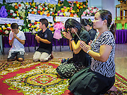 20 AUGUST 2015  - BANGKOK, THAILAND: Women pray at the funeral for Yutnarong Singraw Thursday. More than 100 people gathered at Wat Bang Na Nok in Bangkok for the third day of the funeral rites for  Yutnarong Singraw, a Thai man who was killed in the bombing at the Erawan Shrine in Bangkok Monday. Yutnarong was delivering legal documents when the blast occurred. More than 20 people were killed and more than 100 injured in the blast.    PHOTO BY JACK KURTZ