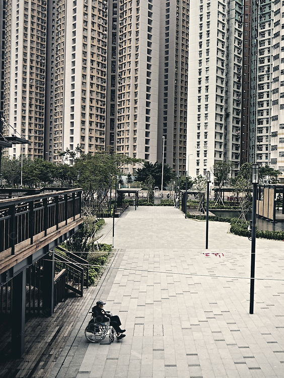 Senior man in wheelchair and other people in Quarter Bay with residential skyscapers as a backdrop in Hong Kong
