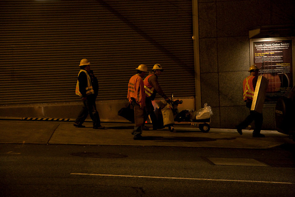 The original capture for a digital painting of a worker with yellow hard hat and reflective vest walking down hill past a door with parallel horizontal lines