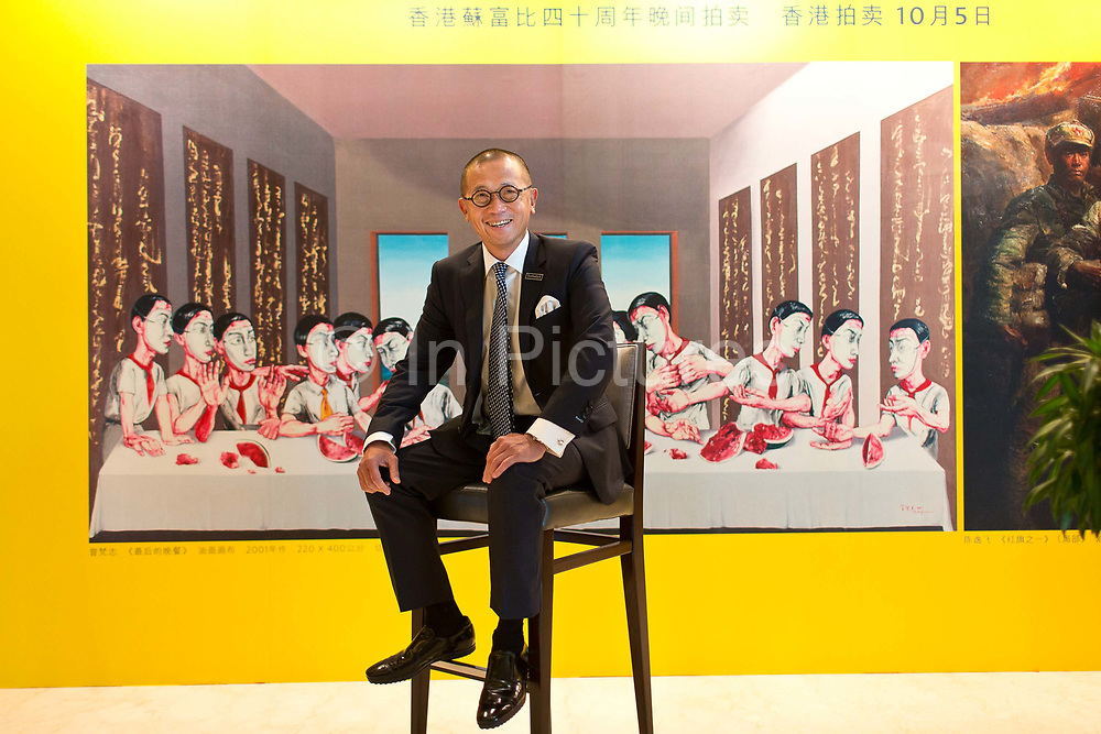 """Dennis Ching, chief executive officer of Southeby's China, poses for a photograph in front of a poster featuring Zeng Fanzhi's The Last Supper, outside of a company event in Shanghai, China September 04,  2013. Both Southeby's and Christie's have opened an office in Mainland China in the past year, however they face overwhelming odds as China's state-owned auction houses such as Poly and Jiamu enjoys a near monopoly over China's art procurement market as foreigners are not allowed to buy vaguely defined """"historical"""" art."""