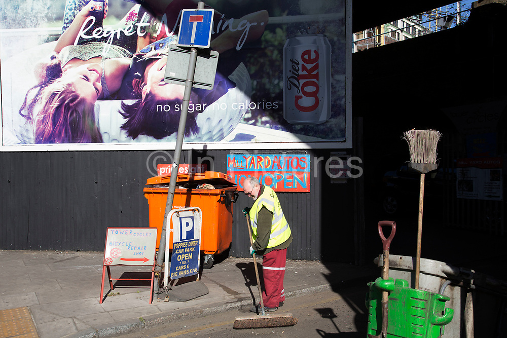 Street cleaner sweeping near an advertising billboard on a street corner on Cable Street, London, UK.