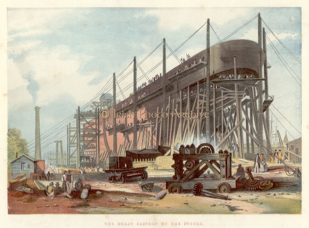Great Eastern' on the stocks in John Scott Russell's (1808-1882) yard at Millwall on the Thames. View from the stern.  Double-hulled, of all iron construction, and powered by four steam engines driving both paddle wheels and screw propeller, she was intended for the passenger trade between Britain and Australia and India.  After a few troubled passenger voyages she was sold for £25,000, a fraction of the building cost of probably £500,000, and converted to a cable laying ship  In this role she was used in laying the Atlantic Telegraph Cable in 1865-1866, and other similar projects. She was Isambard Kingdom Brunel's (1806-1859) last great project.  He collapsed on her deck on her launch in 1858 and died a few days later.  From 'The Illustrated London News'. (London, 7 November 1857). Chromolithograph.