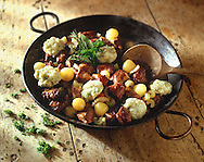 Beef Stew & herby dumplind in a black pan on a wood background with scattered herbs