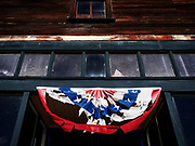 Image of a torn American banner in the North Cascades town of Roslyn, Washington, Pacific Northwest by Randy Wells