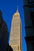 Looking up at the famous Empire State Building, with a blue sky, in New York City