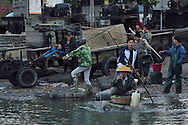 The fishermen of Shi Ma Jiao harbour setting out to sea to their fishing boats, using frigolit styrofoam blocks as rafts for the transportation at high tide, Guangdong province, China