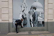 Woman bends down to tie a shoelace beneath a fashion poster showing a fashion couple and St Paul's Cathedral.