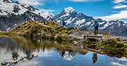 The peak of Aoraki / Mount Cook (3755 meters / 12,349 feet) reflects in a tarn atop the Sealy Tarns Track, in Aoraki / Mount Cook National Park, Southern Alps, Canterbury region, South Island, New Zealand. Glacier-clad Mt Sefton rises on the left. In 1990, UNESCO honored Te Wahipounamu - South West New Zealand as a World Heritage Area. This image was stitched from multiple overlapping photos.