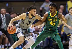 Mar 7, 2020; Morgantown, West Virginia, USA; West Virginia Mountaineers guard Jermaine Haley (10) dribbles and is defended by Baylor Bears guard Davion Mitchell (45) during the first half at WVU Coliseum. Mandatory Credit: Ben Queen-USA TODAY Sports