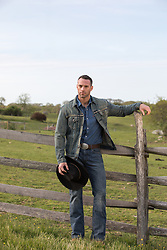 cowboy by a spilt rail fence on a ranch