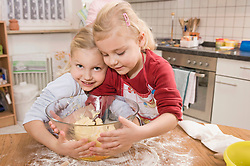 Family preparing cookies in kitchen, smiling