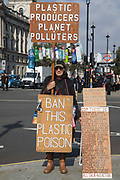 An environmental protester stands on the corner of Parliament Square holding signs calling for a ban on the use of plastics and for action rather than words to tackle the climate emergency at COP26 on 9th October 2021 in London, United Kingdom. The UN Climate Change Conference COP26 is scheduled to be held in Glasgow between 31st October and 12th November.