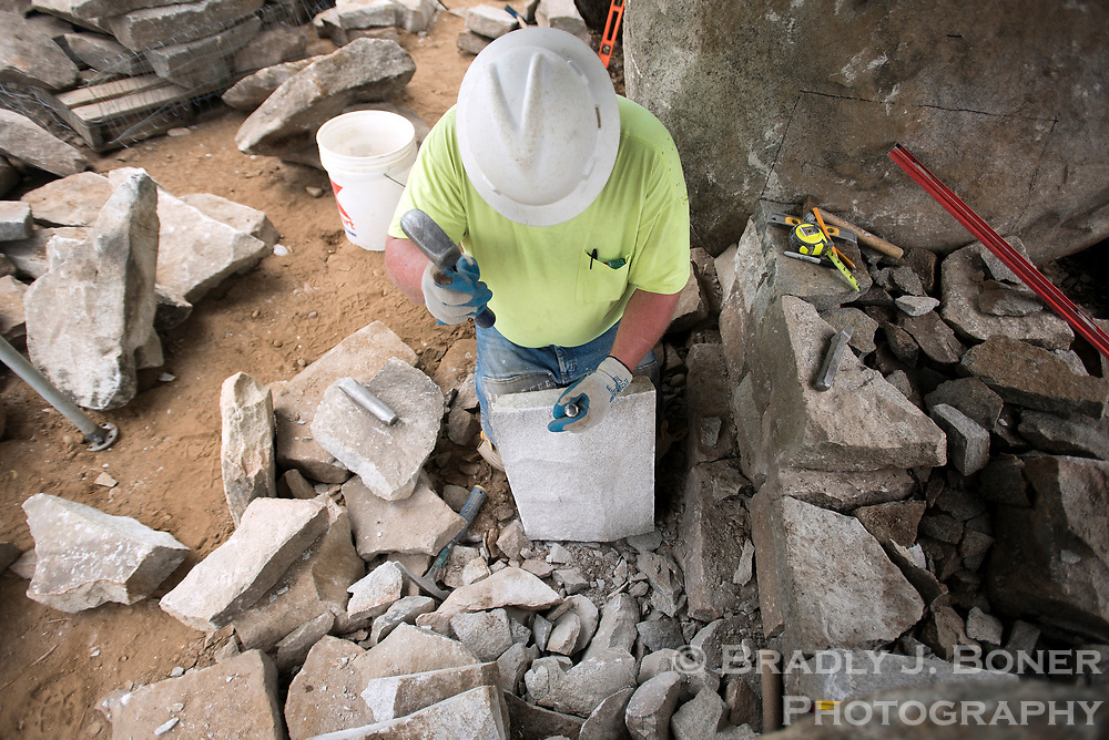 Dan Woolley, of Lexington, Kentucky, chips away at a large stone while building a rock wall last week at the Jenny Lake Visitor Center complex. Professional stone masons from the Dry Stone Conservancy have built several of the structures around the complex since work began four years ago.