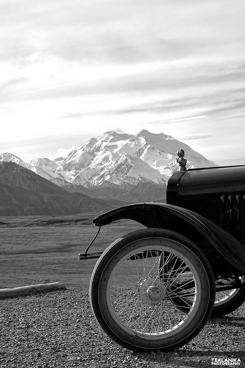 A classic car stops along the Denali Park Road to view the mountain.