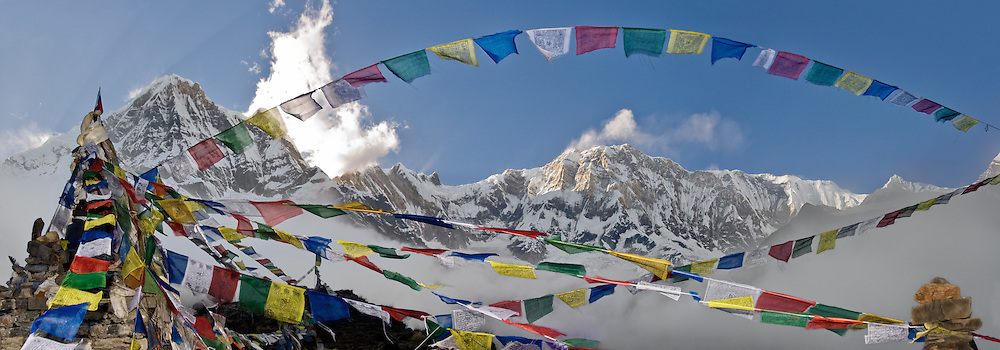 """Prayer flags express compassion at this monument to fallen climbers, at Annapurna South Base Camp (ABC, at 13,550 feet elevation) in the Annapurna Range of Nepal. Annapurna I (center right; 26,545 feet elevation) is the world's 10th highest peak. On the left, Annapurna South (also known as Annapurna Dakshin, or Moditse; 23,684 feet / 7219 meters) misleadingly appears higher due to proximity. Annapurna South was first climbed in 1964 by a Japanese expedition, via the North Ridge. Annapurna is Sanskrit for """"Goddess of the Harvests."""" In Hinduism, Annapurna is a goddess of fertility and agriculture and an avatar of Durga. The panorama was stitched from three images. Published in Wilderness Travel 2010 Catalog of Adventures. Published in """"Light Travel: Photography on the Go"""" book by Tom Dempsey 2009, 2010."""
