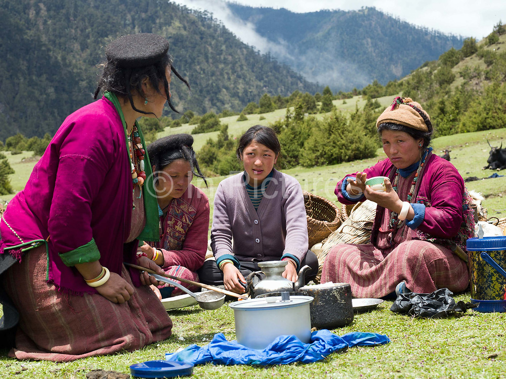 A Brokpa family enjoys lunch whilst preparing to migrate to their summer pastures with their 'zhomo' (male yak and female cow cross), Merak, Eastern Bhutan. The Brokpa, the semi-nomads of the villages of Merak and Sakteng are said to have migrated to Bhutan a few centuries ago from the Tshona region of Southern Tibet. Thriving on rearing yaks and sheep, the Brokpas have maintained many of their unique traditions and customs.