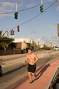 A bare chested jogger running in the cool evening in Miami Beach