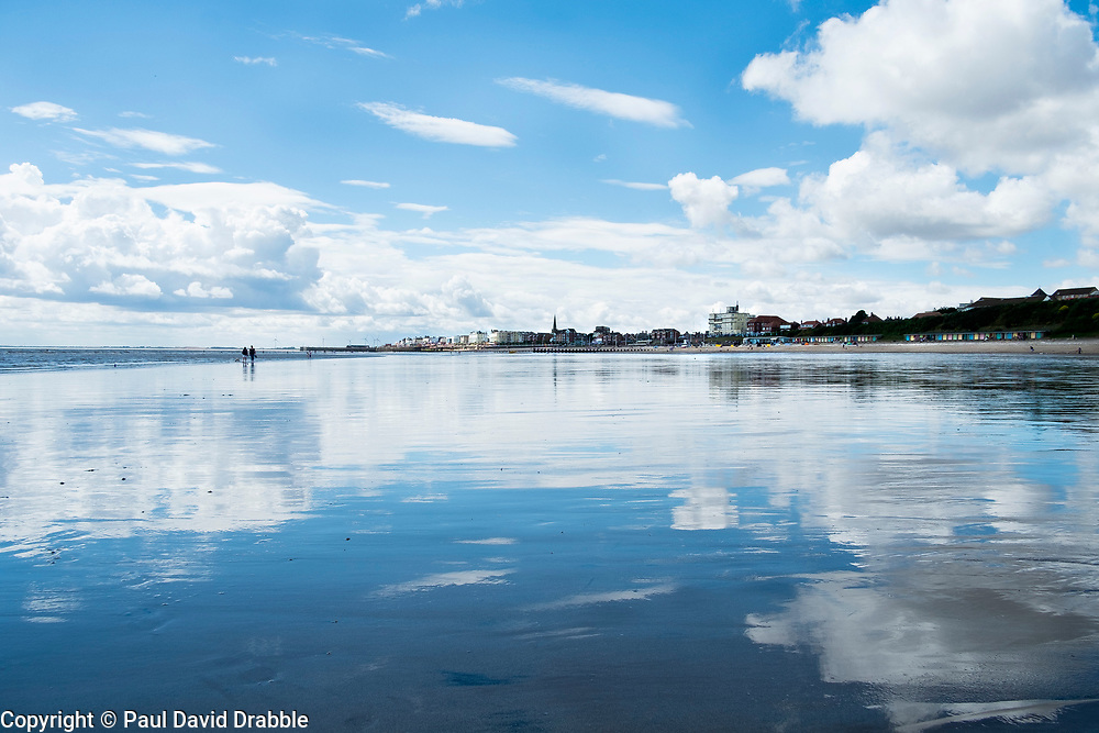 A couple walk on smooth wet North Beach which reflects the clouds from the sky above towards the seaside town of Bridlington West Yorkshire England<br /> <br />  4 August 2016<br />  Copyright Paul David Drabble<br />  www.pauldaviddrabble.photoshelter.com