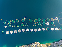 Aerial view of many circular fish farm pools in the beautiful Mediterranean sea, Greece