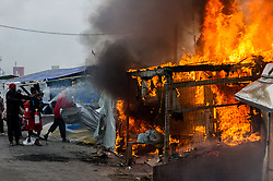 October 26, 2016 - Calais, France - Migrants try to extinguish a burning hut in the Calais Jungle. Huge fires destroyed a mayor part of the refugee camp today. (Credit Image: © Markus Heine/NurPhoto via ZUMA Press)