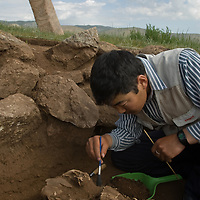 "Mongolian archaeologist Jamsranjav Bayarsaikhan (""Bayaraa"") unearths ancient horse skull in a 2700+ year-old, bronze age  ""khirigsuur"" burial mound at Ulaan Tolgoi archaeological site near Lake Erkhel, north of Muren, Mongolia., Mongolia., Mongolia.  A deer stone of similar age is in the background."