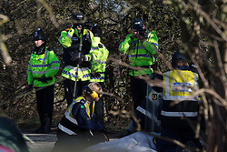 © Licensed to London News Pictures . 11/03/2014 . Barton Moss , Salford , UK . Police photographers photograph as a Police Protester Removal Team cuts a protester away from a metal pipe on the road . Anti-fracking protesters on Barton Moss Road at the Barton Moss protest camp today (11th March 2014) as they have lost a court bid against land owners Peel Holdings to remain on their site . Photo credit : Joel Goodman/LNP