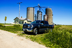 2021 Ford F150 King Ranch Super Crew in Smoked Quartz and Chrome posed in front of Fletcher Elevator in rural McLean County
