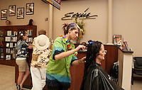 Charlene Bellamo enjoys a tropical Hawaiian atmosphere while getting her hair cut by student Stephanie Dickson during Spirit Week at Empire Beauty School Friday afternoon.   (Karen Bobotas/for the Laconia Daily Sun)