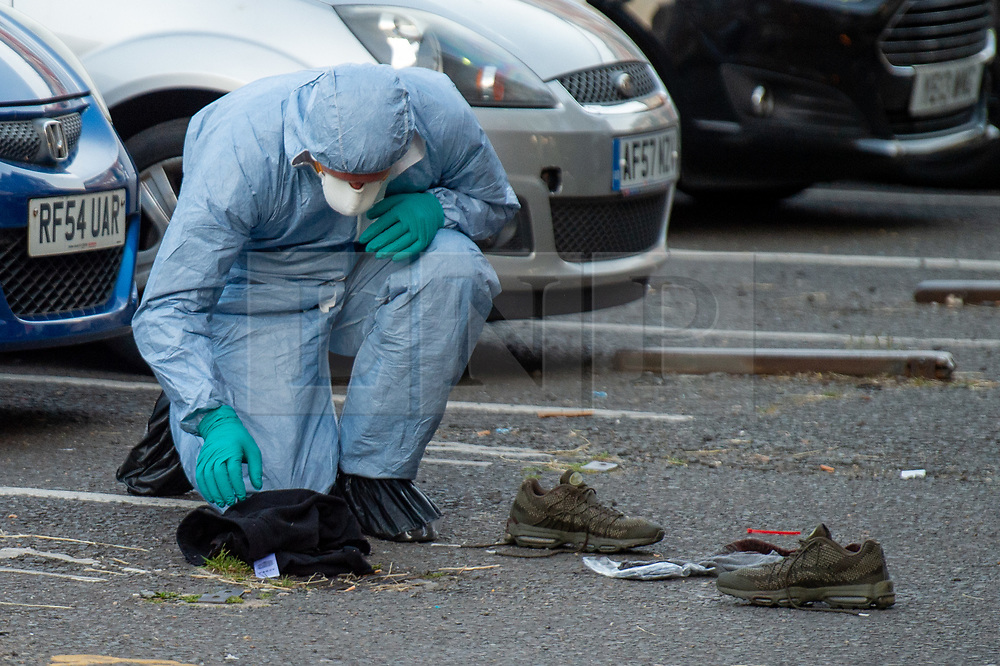 © Licensed to London News Pictures. 20/07/2020. London, UK. A forensic investigator looks over clothes and a pair of shows at the crime scene as police launch investigation after two people were stabbed in Tower Hamlets. Photo credit: Peter Manning/LNP