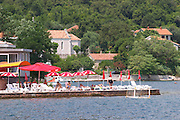 A beach cafe with colourful sun shade umbrellas in Kamenari. Montenegro, Balkan, Europe.