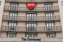 """© Licensed to London News Pictures. 14/02/2018. LONDON, UK. A giant chubby heart balloon is seen The Dorchester Hotel as part of """"Chubby Hearts Over London"""",  a design project conceived by Anya Hindmarch.  Supported by the Mayor of London, the British Fashion Council and the City of Westminster giant chubby heart balloons will be suspended over (and sometimes squashed within) London landmarks as a declaration of love to the city starting on Valentine's Day and continuing throughout London Fashion Week.   Photo credit: Stephen Chung/LNP"""