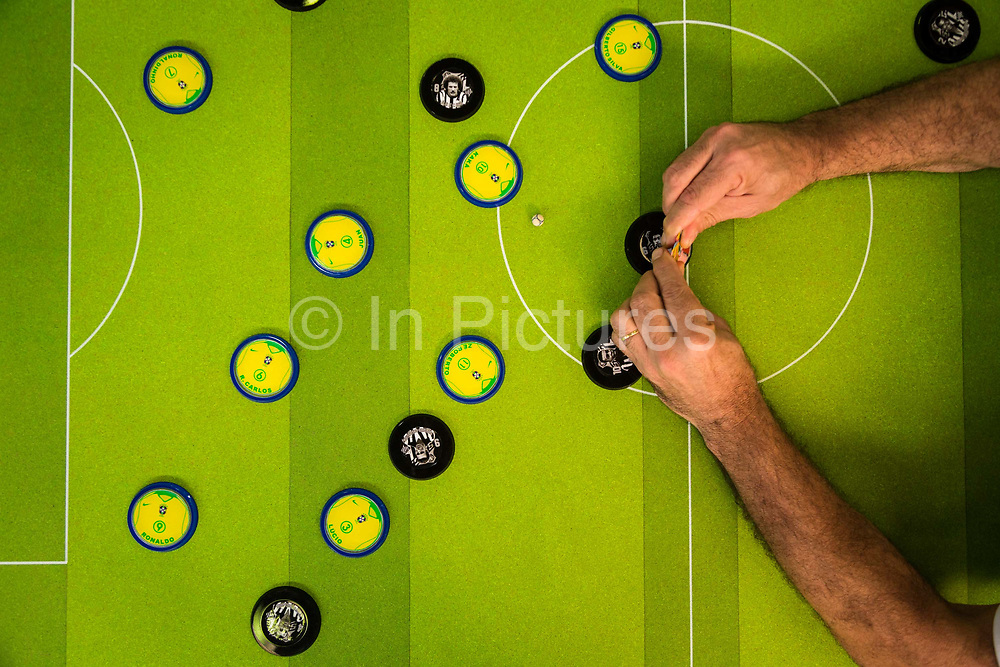 """""""Button"""" football being played at a state championship level in Sao Paulo. It appears to have its origins both  in Hungry and Brazil. The game is played on a smooth, flat surface with markings per a regulation football field. Typical dimensions of the table would be 1.84 m long by 1.20 m wide, with the field being 1.67 m by 1.04 m. Goals are typically 12.5 cm wide by 5 cm tall per the interior dimensions.<br /> <br /> Typical ball, buttons, and goaltender game pieces<br /> Each team consists of 11 pieces, 10 field pieces, or buttons, in the form of small circular disks, and 1 goaltender piece in the form of a rectangular block. At the opening kickoff, all 11 pieces are relegated to their respective sides. Button are always circular in shape. Button football was introduced in 1922 in Brazil and remains as popular as ever. 2013"""