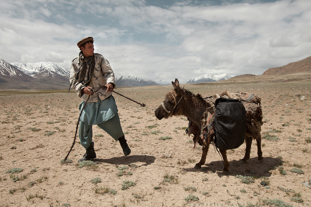 An Afghanistan Border Police soldeir is patrolling the borders between Tajikistan and China. His equipment is carried by a donkey...Trekking through the high altitude plateau of the Little Pamir mountains (average 4200 meters) , where the Afghan Kyrgyz community live all year, on the borders of China, Tajikistan and Pakistan.
