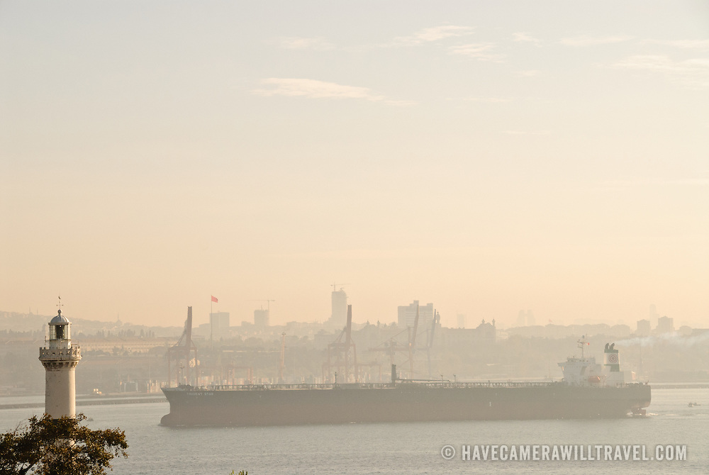 A large cargo ship passes through the narrow intersection of the Sea of Marmara, the Golden Horn, and the Bosphorus Strait, passing very close to a lighthouse in Istanbul, Turkey.