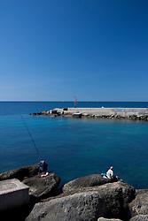 Due persone anziane pescano con la canna all'entrata del porto di Gallipoli (LE)