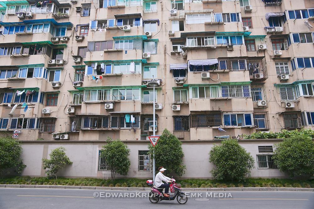 Woman riding an electric bike by an apartment building in Hangzhou, China 2009.