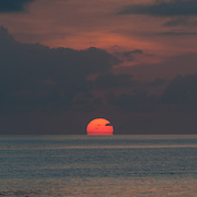 The sun is partly below the horizon, with the calm waters of the Pacific Ocean in the bottom of frame and the orange clouds above. Taken at Swains Reef on the southern end of the Great Barrier Reef of the coast of Queensland, Australia.