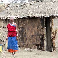 Sanaiyan, poses for a picture as she cleans the compound. <br /> In most homes there are two or more wives and domestics duties are shared amongst the girls and women of that Boma (homestead).<br /> While the girls and younger women are tasked with the more heavier tasks, the gugus who are the elderly women, are tasked with taking care of their grandchildren and cooking.