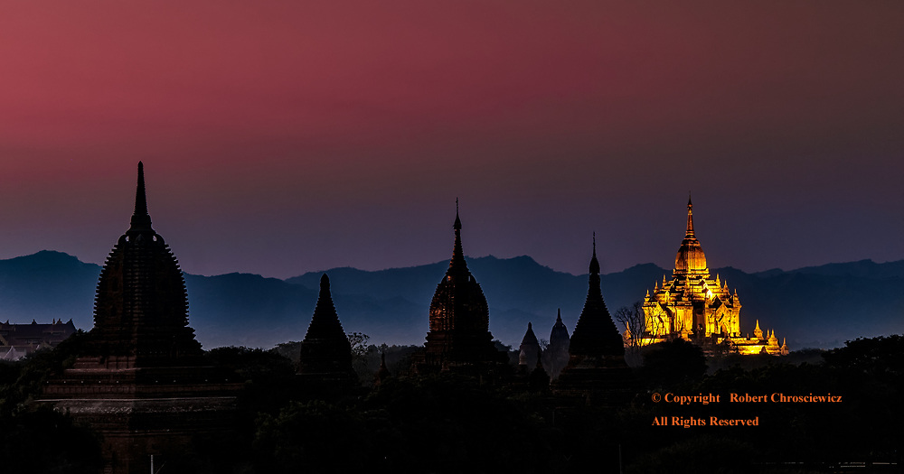 Silhouettes at Dusk: In the latter moments of a red dusk, silhouettes of a series of Buddhist temples lead back to an illuminated Thatbyinnyu Temple, Bagan Myanmar.
