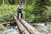 "Carol crosses Chalice Creek on a primitive log bridge in Bugaboo Provincial Park, in the Purcell Range of the Columbia Mountains, British Columbia, Canada. Most tourists are attracted by nearby Canadian Rockies parks along fast paved highways and skip gravel logging roads, thereby leaving the spectacular ""Bugaboos"" as a quiet retreat for hikers, climbers, and luxury CMH helicopter guests. Directions: From Brisco (about 44 kms north of Invermere on Hwy 95), follow signs to Bugaboo Provincial Park and CMH Lodge on a gravel logging road. After 47 kms, turn right on a rougher road to reach Cobalt Lake trail head and Kain Hut trail head, or continue straight along Bugaboo Forest Service Road. Before you reach the gate of luxury CMH Bugaboo Lodge, a left turn crosses Bugaboo Creek bridge: then a left reaches Bugaboo Septet Recreation Site (4 primitive campsites in a free, user-maintained campground reachable by 2WD vehicles) or straight up takes 4WD vehicles and hikers to Chalice Creek trailhead."